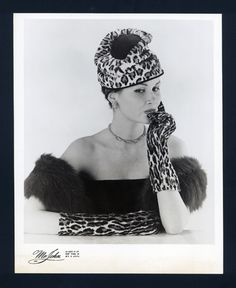 Misbehaving is the name that New York celebrity milliner, Mr John, gave to the ensemble of leopard skin and velour toque hat, fox stole and matching gloves depicted in this phototgraph. The photograph was part of a press release consisting of two booklets and four photographic prints for Mr John's Regency Collection for Autumn and Winter 1957.