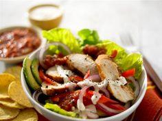 Gebratenes Hühnchenfleisch, angerichtet auf einem köstlichen Avocado-Salatbett, verfeinert mit Limetten-Dressing und saurer Sahne.
