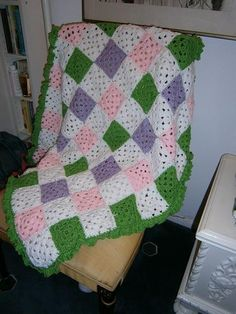 """This beautiful baby blanket is made from 5x5""""  crochet size squares.sewn together.The edging is outlined in a ruffle of spring green yarn.This was made with Red Heart yarn 4 ply.Will sure to keep your little darling boy or girl warm with the coming fall months.Size is 32 x 37'"""