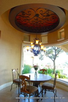 DIY version: Buy a round iron grate from garden or craft store, attach to ceiling, then hang chandelier from center.