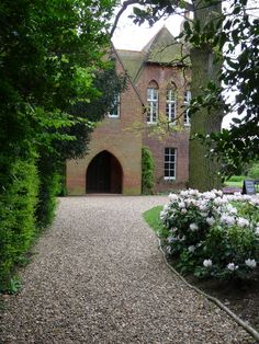 front entrance to Red House | A gravel path leads past an azalea bush to the front porch of Red House, the Bexleyheath home built for William Morris by architect Philip Webb in 1859. Access to the house (owned by National Trust) is through a smaller door at the rear.