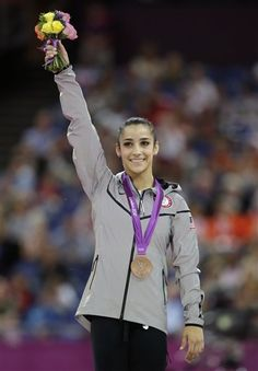 Team USA's Aly Raisman waves from the podium after winning the bronze medal in the women's gymnastics balance beam event final at the London Olympics.