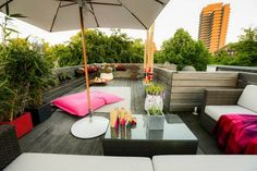 aménager une terrasse d'appartement avec coussin de sol rose, meubles en résine tressée et plantes vertes