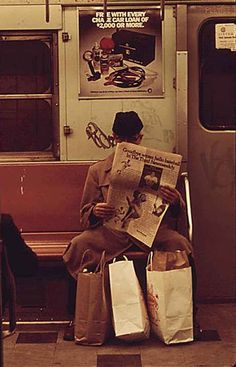 A older man reading the newspaper on the subway. | 32 Revealing Photos Of New York City In The 1970s