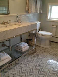Look at those floors! Herringbone tile floors in the bathroom makes a huge statement in a monochromatic style. TileBar has this tile in several colors to match any style.
