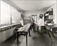 """A tea taster's room with three Chinese employees presiding over long rows of matched cups of brewed tea and dishes containing leaf tea—the tea taster's or """"expectorator's"""" vessel (amounting to a glorified spittoon) is the hourglass-shaped device at lower left."""