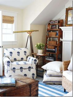 Blue Striped Dhurrie Rug, chest as coffee table, window shade, fireplace, bookcases, floor cushions, reading chairs