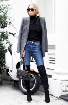 Turtleneck preta com blazer combinados com calça jeans e bota over the knee preta.