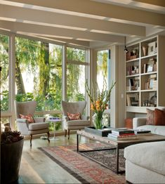 Floor to ceiling windows, high ceilings, exposed beams, built-ins, all one color so the structure recedes and the view and accessories pop.
