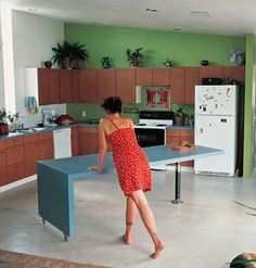 Countertop rolls into the kitchen for food preparation space and then rolls out into the remainder of the room to create a dining table.