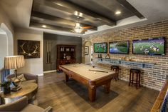A brick accent wall and dramatic beams add a timeless look to this new home built by Ashton Woods Homes. The Ridgeview community. Austin, TX.