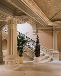 Graceful limestone staircase with a custom decorative handrail that terminates into a sculptural bronze luminaire