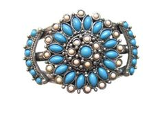 Beautiful Silver Tone Metal Cuff Bracelet with an Ornate Flower Design of Chalk Turquoise and Alabaster Gifts By Lulee. $19.99. Silver base metal - cuff style fits most wrists. Chalk turquoise (dyed/stabilized). Ornate flower design. Organza bag