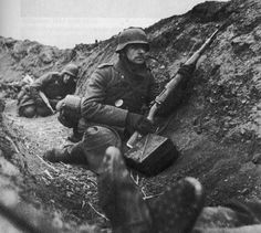 German soldiers await the order to attack, with fallen comrade next to them. Eastern front, 1943.