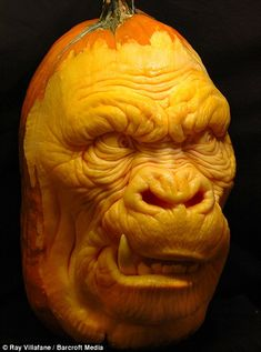 A gorilla face carved out of a pumpkin using spoons and scalpels
