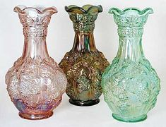 3 medium length carnival glass vases. Pink, amber and emerald.