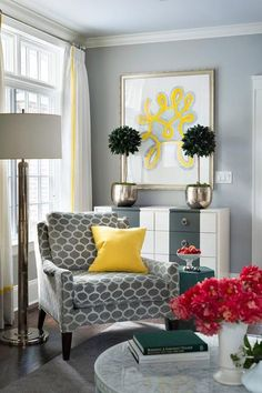 Yellow and gray living room features a gray corner reading chair adorned with a canary yellow pillow next to an emerald green accent table illuminated by a polished nickel floor lamp placed in front of a gray stripe dresser topped with hammered metal planters under yellow art.