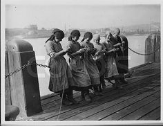 Holyhead, Angelsey, Wales, UK --- Welsh women stand and knit whilst waiting for a catch of herring to arrive. Holyhead is one of the biggest centres for the herring industry. --- Image by ? Hulton-Deutsch Collection/CORBIS