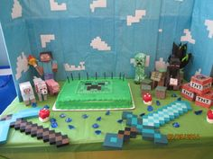 Matthew's Minecraft Themed Birthday Party.  Minecraft cake display.  The guests loved playing with the foam swords, blue acrylic diamond gems, and paper figurines a little too much prior to me taking a photo of the birthday cake display.   = )