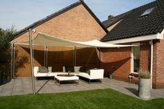 Mooi lounge terras met een Soliday M handbediend schaduwdoek.