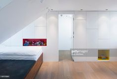 Highbury Loft Conversion, London, United Kingdom. Architect: Azman Architects, 2012. View of entrance from stair with cabinetry and childrens toys.
