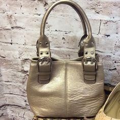 """TIGANELLO GOLD SATCHEL STYLE BAG This purse is so cute and don't let looks deceive you, because even though it appears small it has some width to it. NWOT 11x8 7 strap drop and width measuring on the bottom is 7"""" Tignanello Bags Satchels"""