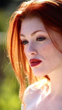 Totally dramatic fire red hair, pale skin and freckles. The lipstick shade rocks with her tone. Loving this look.