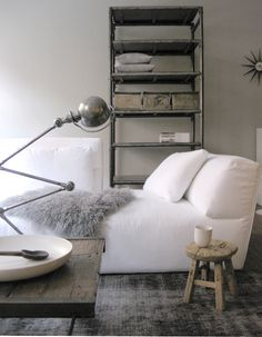 Crisp white bed, gray carpet, gray throw, bedside rustic stool, rustic table, old articulated desk lamp, industrial shelves, starburst clock
