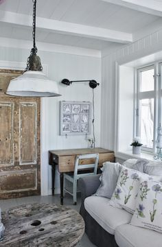 Rustic wood doors, deck and coffee table bring the character to all white room. Mias Interiør