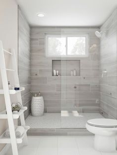 Bliss out in this gorgeous walk-in shower. Ash-gray tile and a Roman wall bound an expansive shower space, featuring a built-in shelf and white clerestory window. Accent the rest of the room white for…More