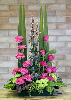 Parallel arrangement with a group of cerise pink standard Carnations, and a group of cerise pink Roses, Cordyline australis leaves, hedera colchica 'Sulphur Heart', Heuchera 'Plum Pudding', green berries of Pieris formosa 'Valley Rose', Chrysanthemum 'Kermit', Hedera helix,  Hedera colchicum 'Sulphur Heart', and Heuchera 'Silver Scrolls' - I really like this ~ by Chrissie Harten - design 117