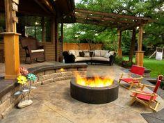 patio avec pergola en bois, foyer rond en pierre noire et transats