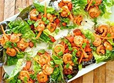 Spicy Asian Shrimp Lettuce Cups1 pound shrimp  2 Tbs. Sriracha sauce  4 cloves garlic, minced  2 Tbs. extra-virgin olive oil  1 head butter or boston lettuce, leaves separated  1 red bell pepper, diced  1 carrot, julienned  3 scallions, thinly sliced  1/4 cup cilantro  1/4 cup soy sauce for drizzling  1 pinch coarse salt and freshly ground pepper  3 ounces thin rice noodles