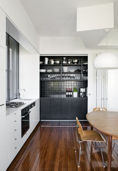 The white doors slide from the right to cover up the black area.   Apartment Podger Holmes - Tribe Studio Architects