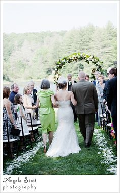 Mother of bride in bright green dress and father of bride walk their daughter down the isle in her outdoor wedding reception at the Inn at Half Mile Farm in Highlands, NC.