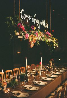 Hanging script above a lush flower box makes for an elegant, unique touch at the head table. Photo by Tec Petaja via 100 Layer Cake