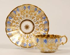 An Imperial Porcelain Factory cup and saucer, Nicholas I period (1825-1855). The fluted cup and saucer decorated in an elaborate gold scroll and vine motif punctuated with blue plume accents; gilt border and gilt interior.