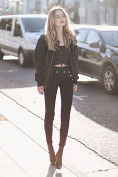 Woman is wearing a black bomber jacket under the black top, paired with skinny jeans and heeled boots. It is easy and looks put-together.