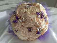 A pretty bouquet for a flower girl with cream roses, pretty lavender and lilac brooches and a string of bling wrapped around the handle. The base of the bouquet has a pretty skirt of purple tulle.  All bouquets can be reproduced in the size and colour of your choice. Feel free to mix and match ideas to make your bouquet more individual. Corsage, MOB and Lapel pins are also available to match your colours. Contact leeann@bejewelledbridal.com.au for more information.