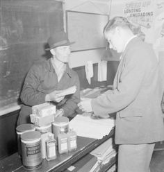 """Boatman Ronald Hambridge (left) collects his rations from the headquarters of the Grand Union Canal Carrying Company at Hayes in Middlesex. The original caption explains that canals workers are greatly affected by food rationing because they are unable to register with one particular shop. Instead, """"at Hayes they are issued travellers vouchers, obtain supplementary tea sugar and dried milk because of the heavy nature of their work, get orange juice for their children""""."""