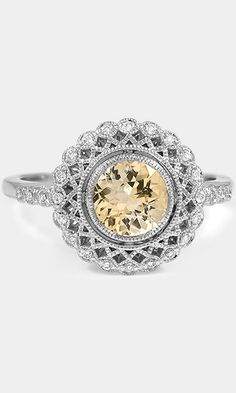 This truly exceptional vintage-inspired ring encircles a bezel set diamond with lavishly detailed latticework and a halo of shimmering diamonds. Diamonds sparkle along the shoulders, a beautiful design embellishes the gallery, and the halo shimmers with milgrain detail.