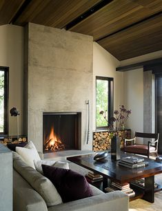 home, residential, concrete, living room, mahogony window frames, gray couch, purple pillow, fireplace, cut wood bins