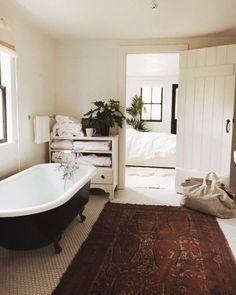 cozy off-white bathroom, black clawfoot tub, hexagon tile floors, antique rug