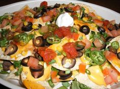 Ingredients    Tortilla Chips  1/2 cup sliced tomatoes  About 10 sliced black olives  1 1/2 green onion  1 jalepeno  1/2 cup fresh grilled corn  1/4 bunch of roughly chopped cilantro  1/3 cup Nacho cheese sauce  3 tbs salsa  3 tbs sour cream  1 tsp cumin