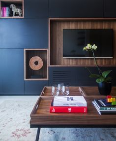 A custom media unit with hickory detailing features built-in shelves for displaying objects.
