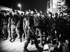 Anti riot police, wearing helmets and clutching shields
