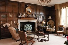 living room with wood paneling and a Tudor arch stone fireplace - photo by David Merewether - styling by Julie Simpson