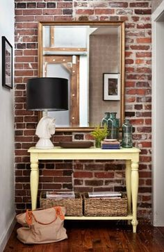 Capella Kincheloe Interior Design: Small foyer hall with exposed brick wall, mirror, butter yellow console table with ...