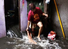 A woman watches floodwater flow into a house following a dike breach caused by the storm, on August 3, 2012 in Navotas City, north of Manila, Philippines. (AP Photo/Pat Roque)