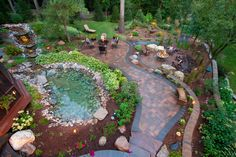 This enchanting paver patio features a pathway around a natural stone pond, a sunken fire pit space surrounded by brown Adirondack chairs, and shrubbery in a mulched garden area. Neutral tufted wrought-iron seats surround a circular glass table.